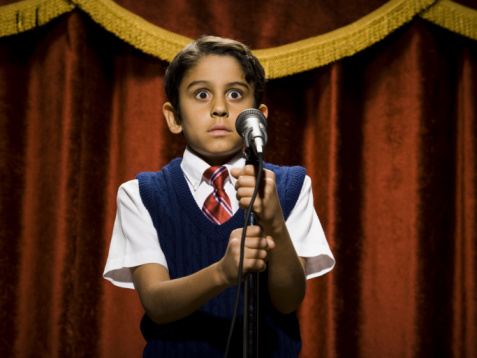 Boy standing on stage with microphone and big eyes